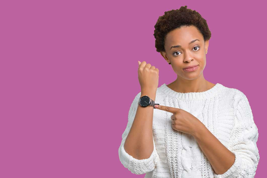 Woman pointing to watch suggesting not to delay fibroid treatment